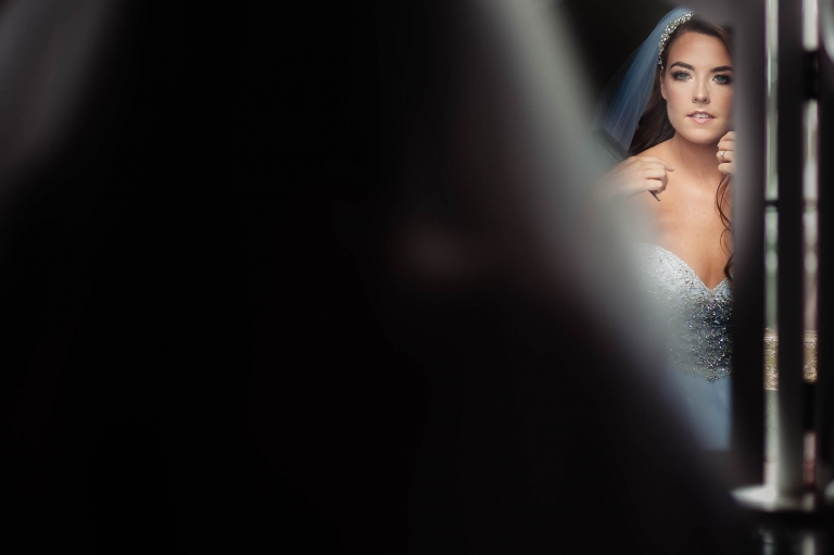 Bride looks into mirror after putting her dress on