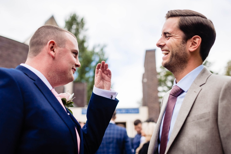 Groom shares a joke with a guest at the church