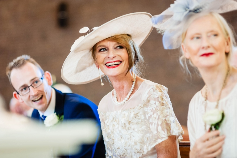 Mother of the groom smiles as she watches the bride enter the church