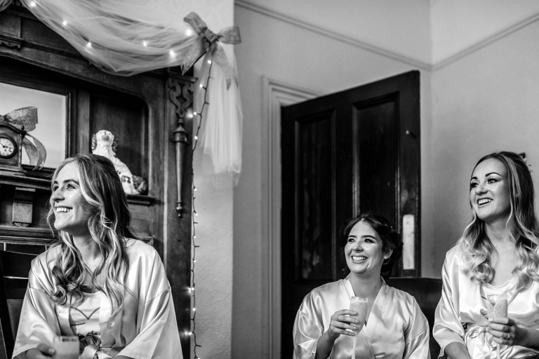 Bridesmaids share a joke with the bride