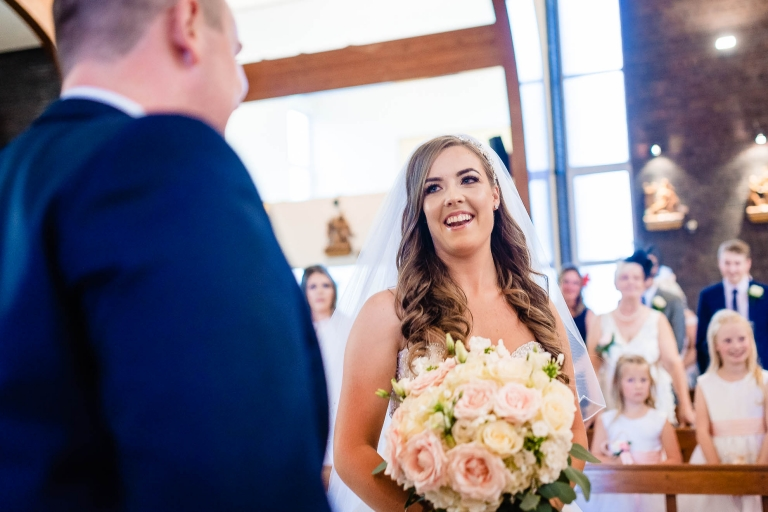 Bride smiles at the groom as she arrives at the altar
