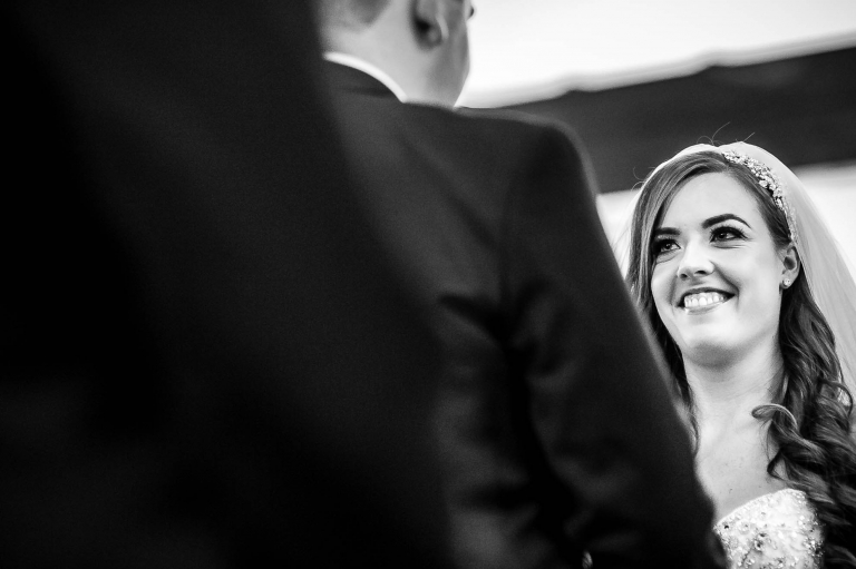 Bride smiles at the groom during the exchange of rings
