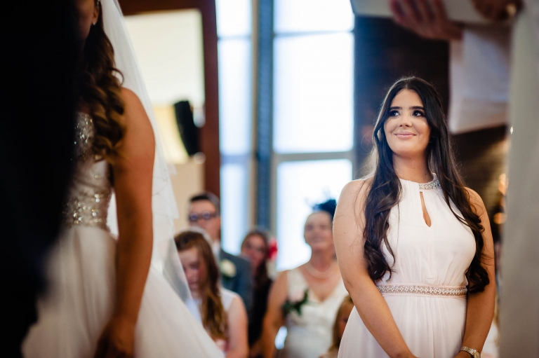 Bridesmaid smiling as she watches the bride and groom during the ceremony