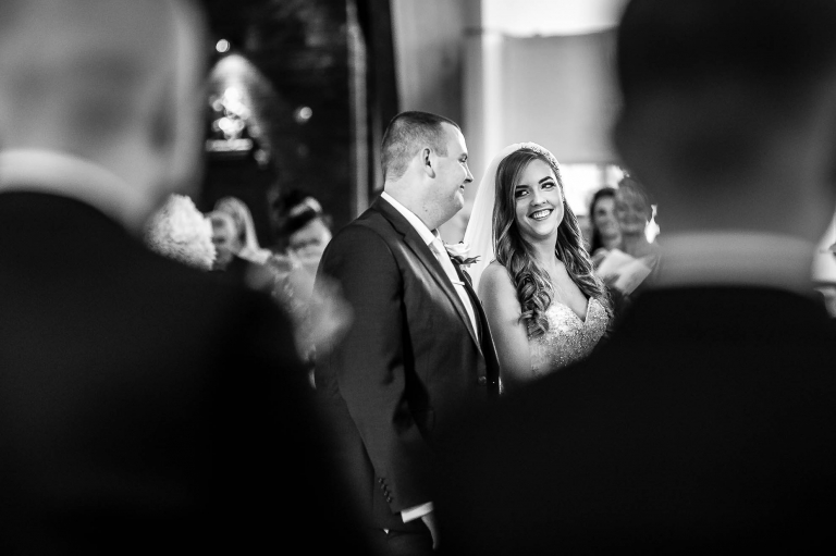 Bride and groom smile at each other during the ceremony