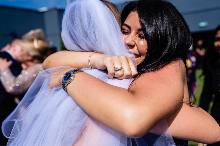 bride gets a big hug from a wedding guest
