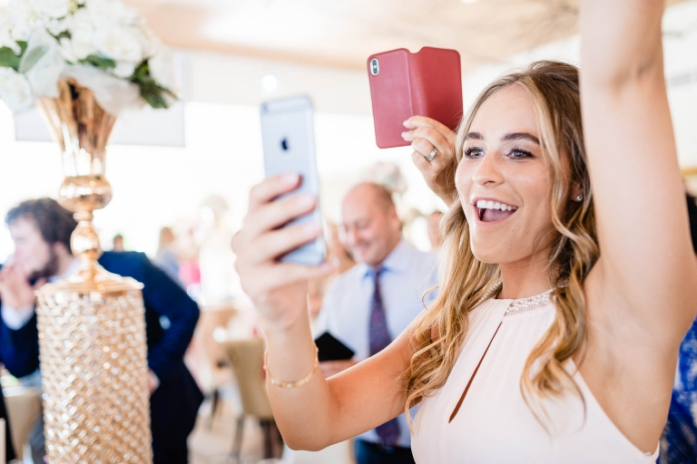 Bridesmaid cheers as bride enters wedding breakfast