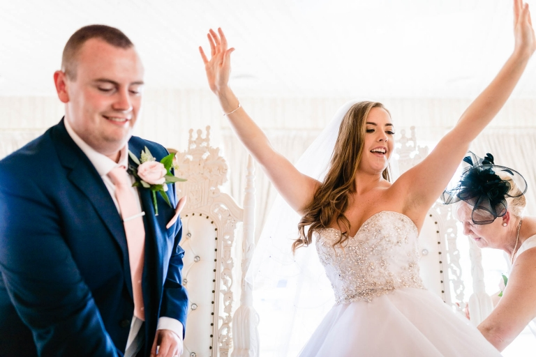 bride wih hands up in the air as she sits at the top table