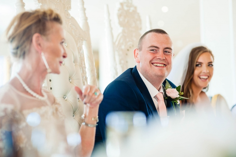 Groom laughs at the best mans joke during the speeches