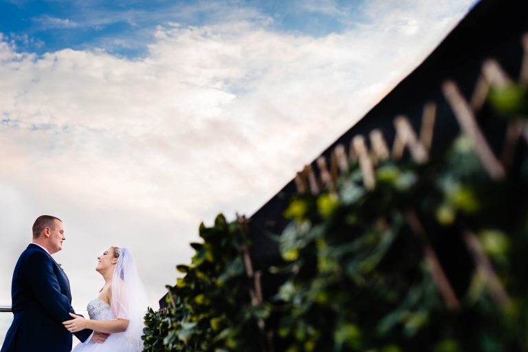 Bride and groom hold each other on the roof terrace