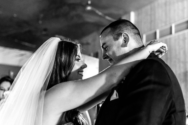 Bride and groom smile at each other during first dance