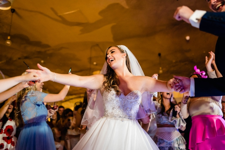 Bride and groom hold hands with guests while dancing