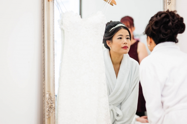 Bride looks at her reflection in mirror