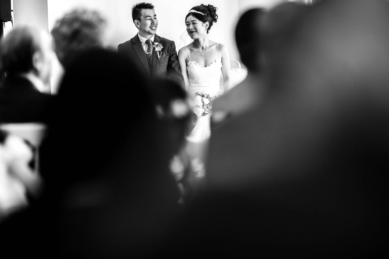 Bride looks at groom and smiles during wedding ceremony