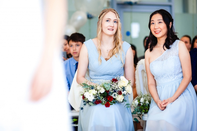 Bridesmaids smile during wedding ceremony