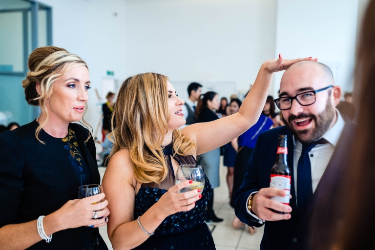 Woman wedding guest taps male guest on head
