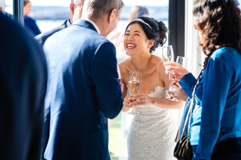 Bride shares a joke with wedding celebrant during drinks reception