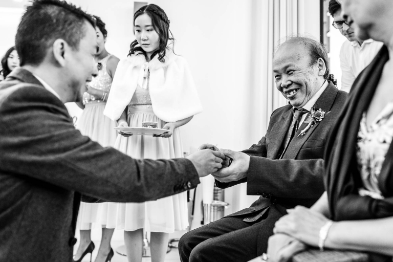 Groom gives his father tea during the tea ceremony