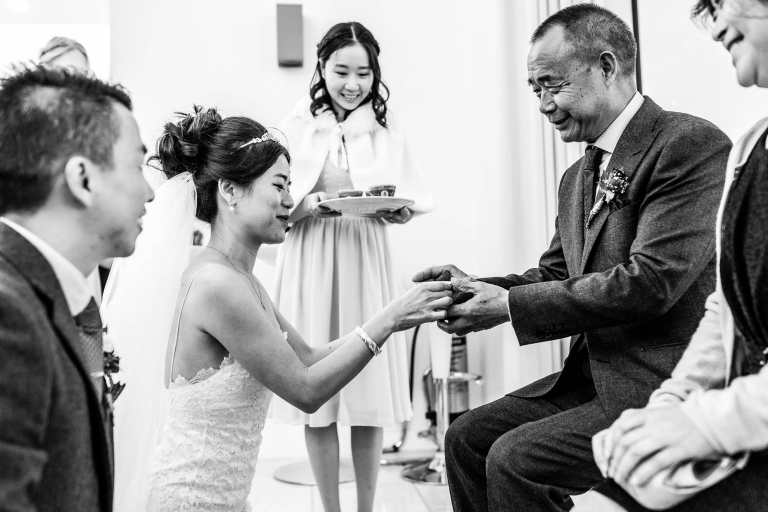 Bride gives her father tea during tea ceremony
