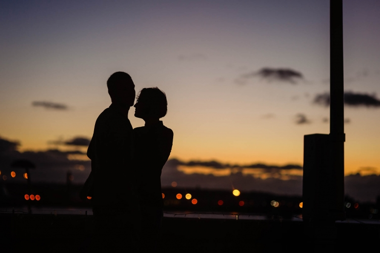 Silhouette of couple behind sunset sky