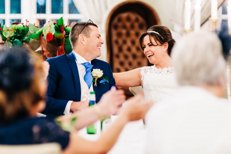 Bride and groom share a joke during speeches