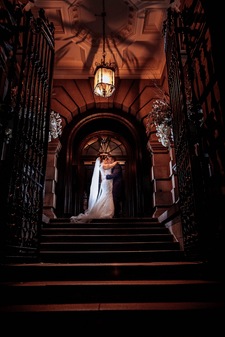 Bride and groom kiss on the stairs of 30 James street