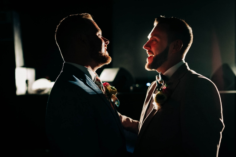 Same sex couple smile together during first dance