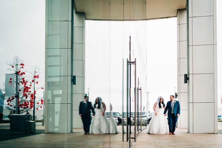 Bride and groom walk together past Hilton hotel