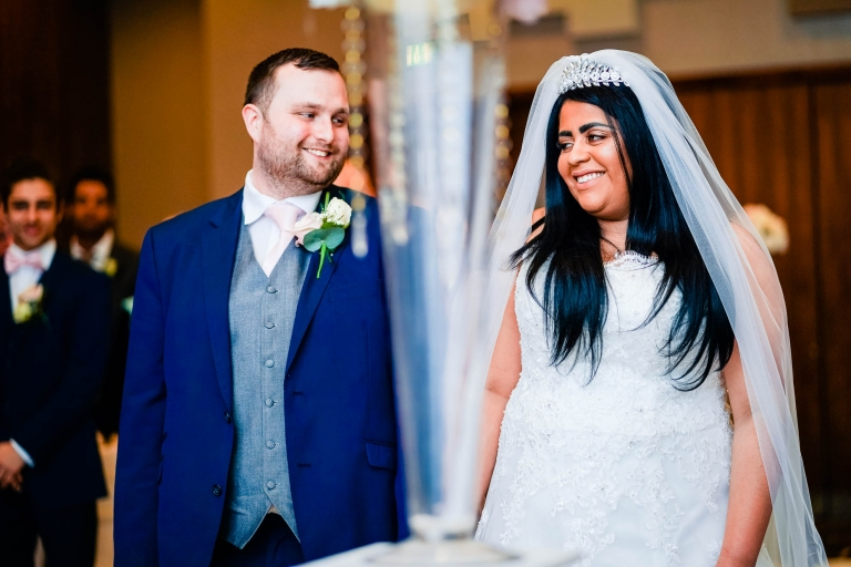 Bride and groom smile together during ceremony