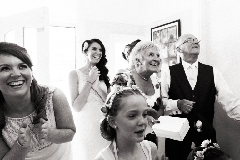 Brides family and bridesmaids see bride in dress for the first time