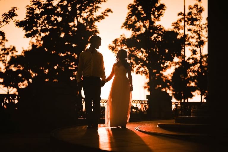 Bride and groom walk together at sunset
