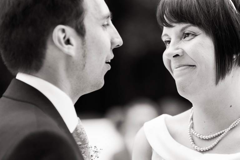 Bride and groom smile during exchange of vows