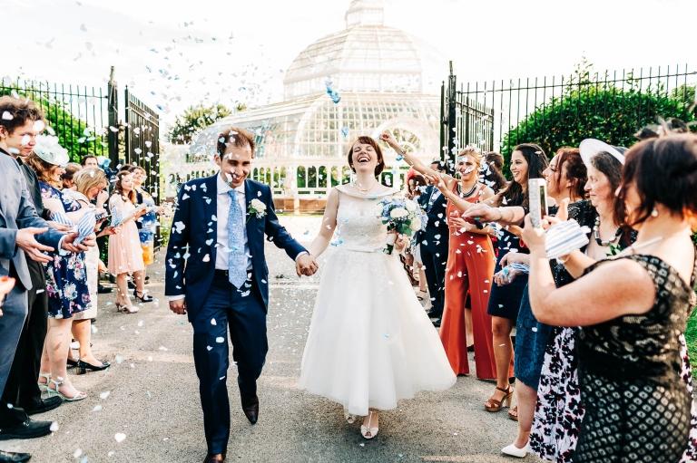 Bride and groom walk through confetti throw