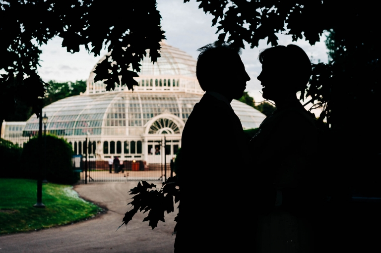 Bride and groom silhouette outside Palm House