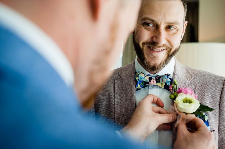 Groom adjusts lapel flower