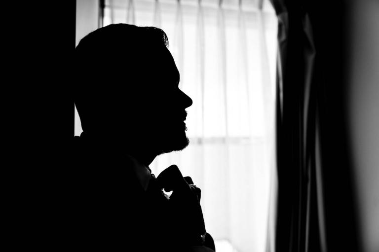 Groom silhouette as he adjusts his tie