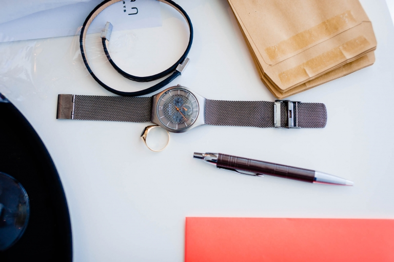 A watch and pen on a table