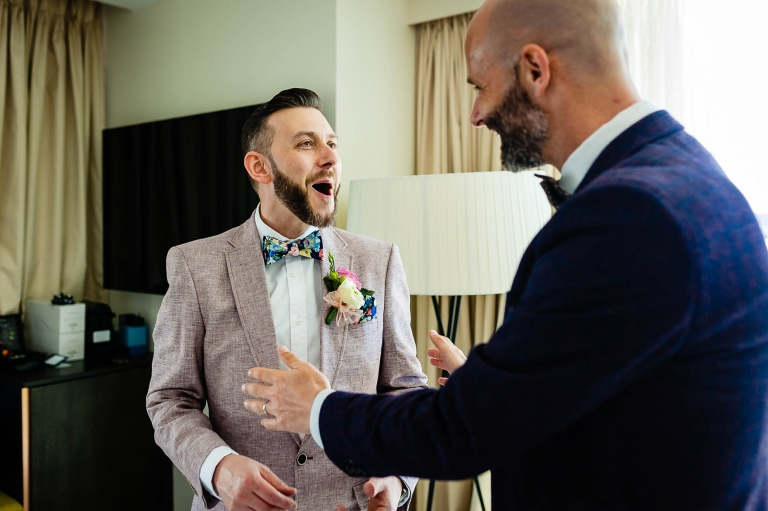 The groom shares a joke with a guest