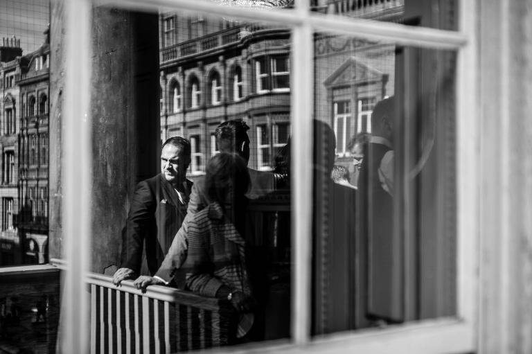 Guest reflection in window on town hall balcony