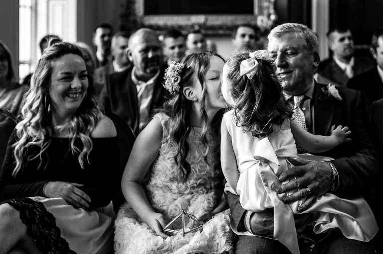 Flower girl gives big sister a kiss during the exchange of rings