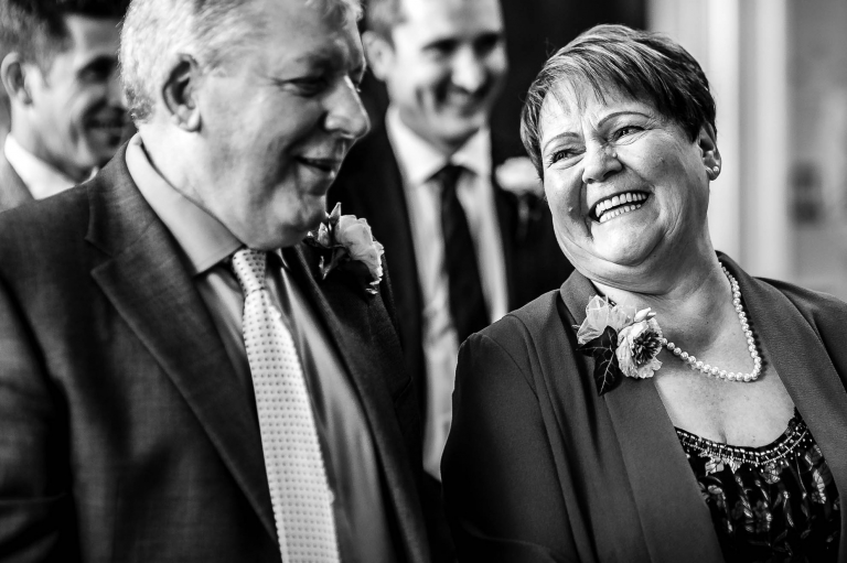 Grooms mum and dad smile at each other during ceremony