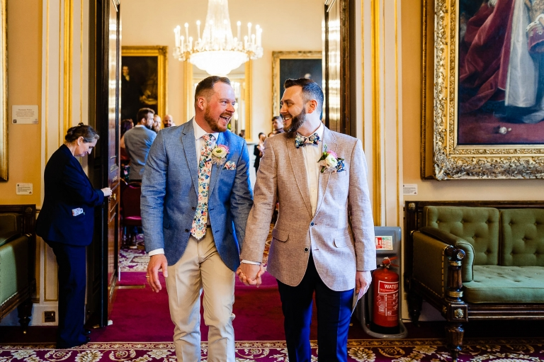 The newlyweds laugh together as they walk out of the ceremony room