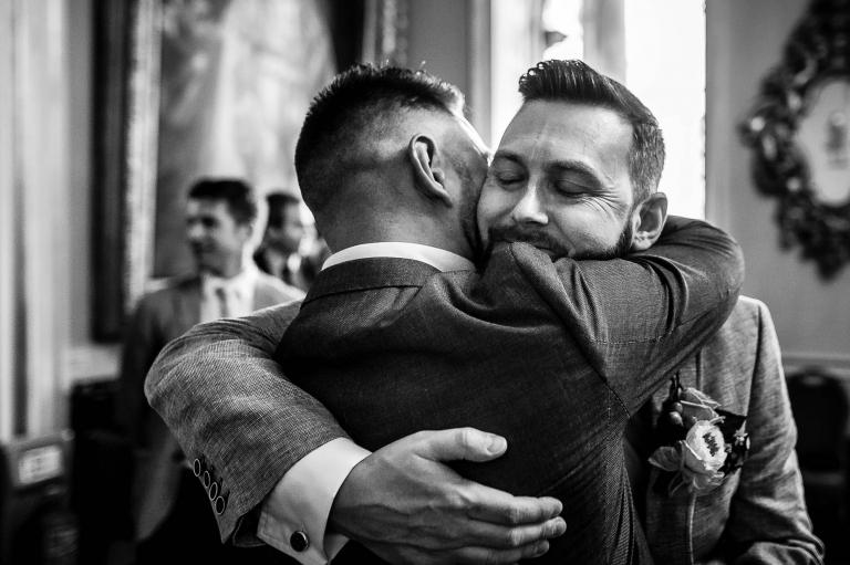 Guest hugs groom after wedding ceremony