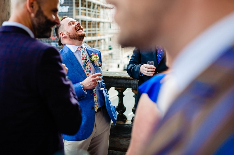 Groom enjoying a drink with guests during drinks reception