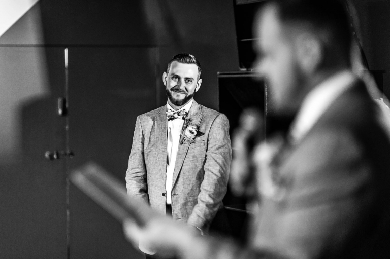 Groom looks over at his partner during the speeches
