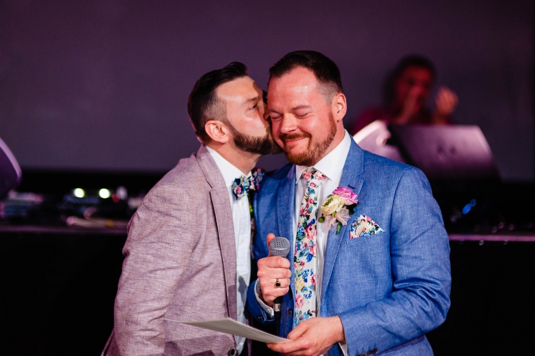 groom gives his partner a kiss during the speeches