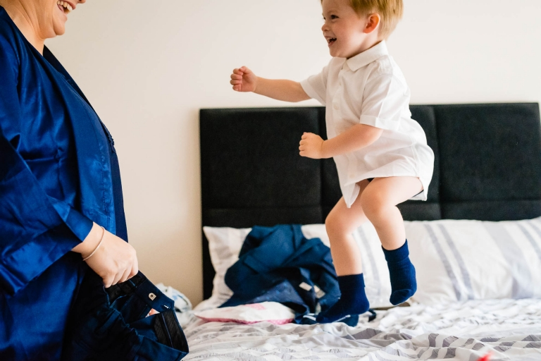 page boy jumping on bed