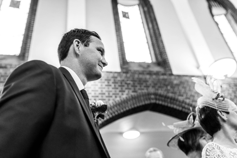 Groom smiles as he watches his bride walk up the ailse