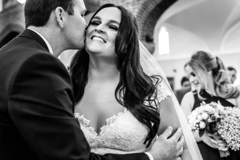 Groom gives the bride a kiss on the cheek