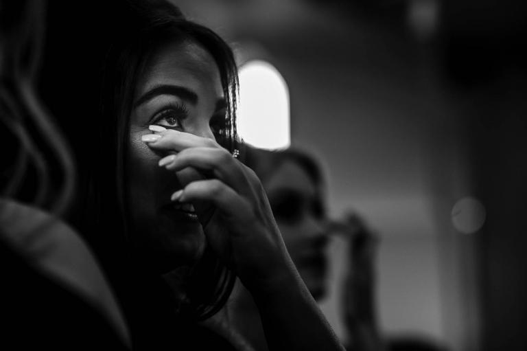 Bridesmaid wipes away tear