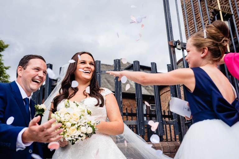Bridesmaid throws confetti over happy couple